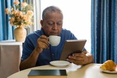 Homme supérieur à l'aide du comprimé numérique à la table dans la maison de repos Photo stock