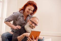 Homme supérieur à l'aide du comprimé numérique avec l'épouse tout près Image libre de droits