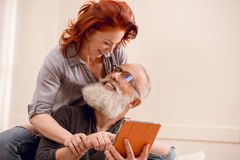 Homme supérieur à l'aide du comprimé numérique avec l'épouse tout près Photo stock