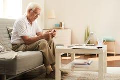 Homme supérieur à l'aide du smartphone à la maison Photos stock