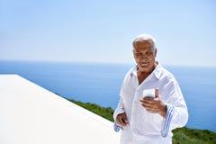 Homme supérieur à l'aide du téléphone intelligent Image stock
