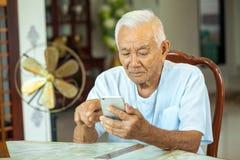 Homme supérieur à l'aide du téléphone portable à la maison Photo libre de droits