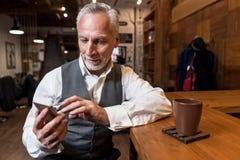 Homme supérieur à l'aide du téléphone portable au compteur de barre Images stock