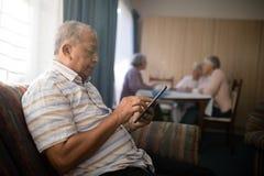 Homme supérieur à l'aide du téléphone portable sur le sofa Photo stock