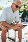 Homme supérieur à l'aide du téléphone portable tout en se reposant dehors Photos libres de droits
