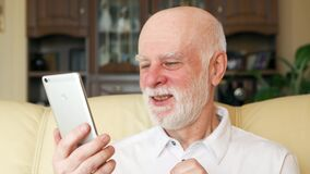 Homme supérieur à la maison utilisant le téléphone portable ayant la causerie visuelle Professeur parlant sur le mobile par l'int banque de vidéos