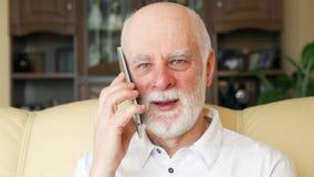 Homme supérieur à la maison utilisant le téléphone portable Professeur parlant sur le mobile Vie moderne active après retraite banque de vidéos