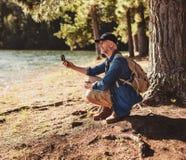 Homme supérieur à un lac utilisant la boussole pour rechercher la direction Image libre de droits