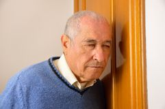 Homme supérieur écoutant derrière la porte Image stock