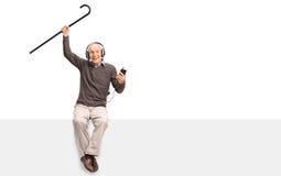 Homme supérieur écoutant la musique sur des écouteurs Photographie stock