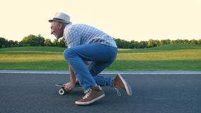 Homme supérieur élégant actif faisant de la planche à roulettes sur le genou banque de vidéos