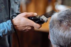 Homme supérieur étant équilibré au raseur-coiffeur Images libres de droits