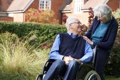 Homme supérieur étant enfoncé le fauteuil roulant par l'épouse Photo libre de droits