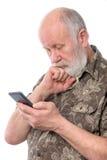 Homme supérieur étonné et confus avec quelque chose au smartphone mobile, d'isolement sur le blanc Photographie stock libre de droits