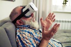 Homme supérieur étonné par des verres de casque de réalité virtuelle Photographie stock