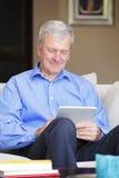 Homme supérieur actif avec le comprimé Photographie stock libre de droits