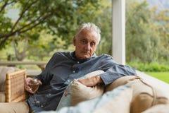 Homme supérieur actif ayant le champagne dans le porche à la maison photo stock