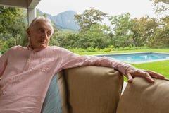 Homme supérieur actif détendant sur le sofa dans le porche à la maison photo stock
