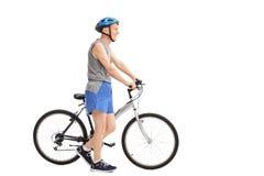 Homme supérieur actif poussant un vélo Photographie stock