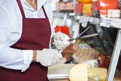 Homme supérieur affilant des couteaux dans la boutique de fromage Photographie stock libre de droits