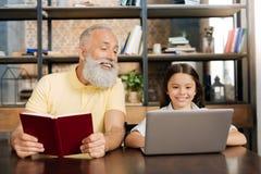 Homme supérieur agréable regardant son écran d'ordinateur portable de petite-filles Photos libres de droits