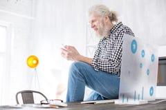 Homme supérieur agréable s'asseyant sur la table et textoter Photographie stock libre de droits