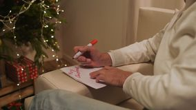 Homme supérieur agréable signant une carte de Noël banque de vidéos