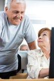 Homme supérieur aidant la femme dans la classe d'ordinateur Images libres de droits