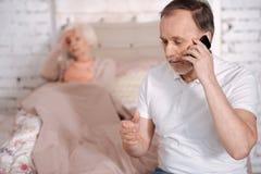 Homme supérieur appelle l'urgence pour l'épouse malade Photos stock