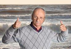 Homme supérieur appréciant l'extérieur avec la mer onduleuse Photographie stock libre de droits