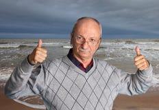 Homme supérieur appréciant l'extérieur avec la mer onduleuse Photographie stock