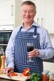 Homme supérieur appréciant la cuisson dans la cuisine avec le verre de vin Images stock