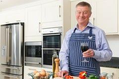 Homme supérieur appréciant la cuisson dans la cuisine avec le verre de vin Photo libre de droits