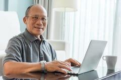 Homme supérieur asiatique à l'aide de l'ordinateur portable Images libres de droits