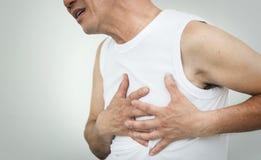Homme supérieur asiatique ayant la crise cardiaque tout en établissant sur le blanc image stock