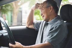 Homme supérieur asiatique ayant le mal de tête de la migraine Photographie stock libre de droits