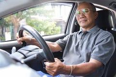 Homme supérieur asiatique décontracté en verres conduisant une voiture Photos stock