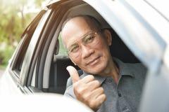 Homme supérieur asiatique décontracté en verres conduisant une voiture Image libre de droits