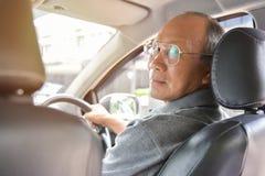 Homme supérieur asiatique décontracté en verres conduisant une voiture Images stock