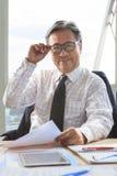 Homme supérieur asiatique d'affaires détendant sur la table de fonctionnement Photo stock