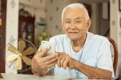 Homme supérieur asiatique heureux à l'aide du téléphone portable Photos stock