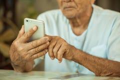 Homme supérieur asiatique heureux à l'aide du téléphone portable Images stock
