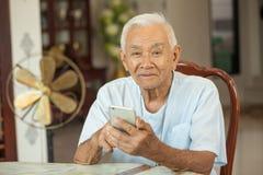 Homme supérieur asiatique heureux à l'aide du téléphone portable Image libre de droits
