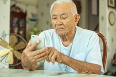 Homme supérieur asiatique heureux à l'aide du téléphone portable Photos libres de droits