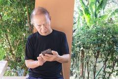 Homme supérieur asiatique heureux à l'aide du téléphone portable à la maison Photo stock
