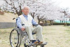 Homme supérieur asiatique s'asseyant sur un fauteuil roulant Photographie stock