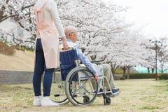 Homme supérieur asiatique s'asseyant sur un fauteuil roulant avec le travailleur social Images stock