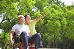 Homme supérieur asiatique s'asseyant sur un fauteuil roulant avec son épouse Image libre de droits