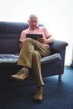 Homme supérieur assis sur un sofa avec des jambes croisées Photos stock