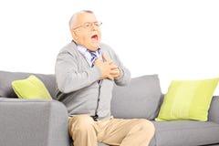 Homme supérieur assis sur un sofa ayant une crise cardiaque Images libres de droits
